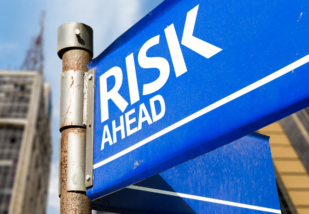 """Blue sign post with """"Risk Ahead"""" printed across it."""